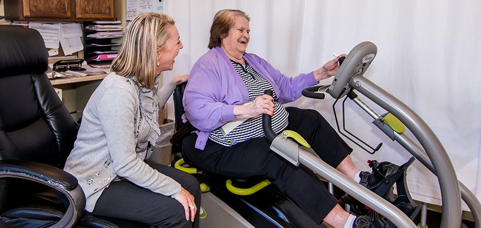 Rehabilitation staff member joyfully assisting a resident with her rehab workout
