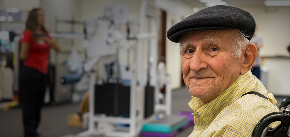 A senior sitting in a wheelchair in a rehab gym.