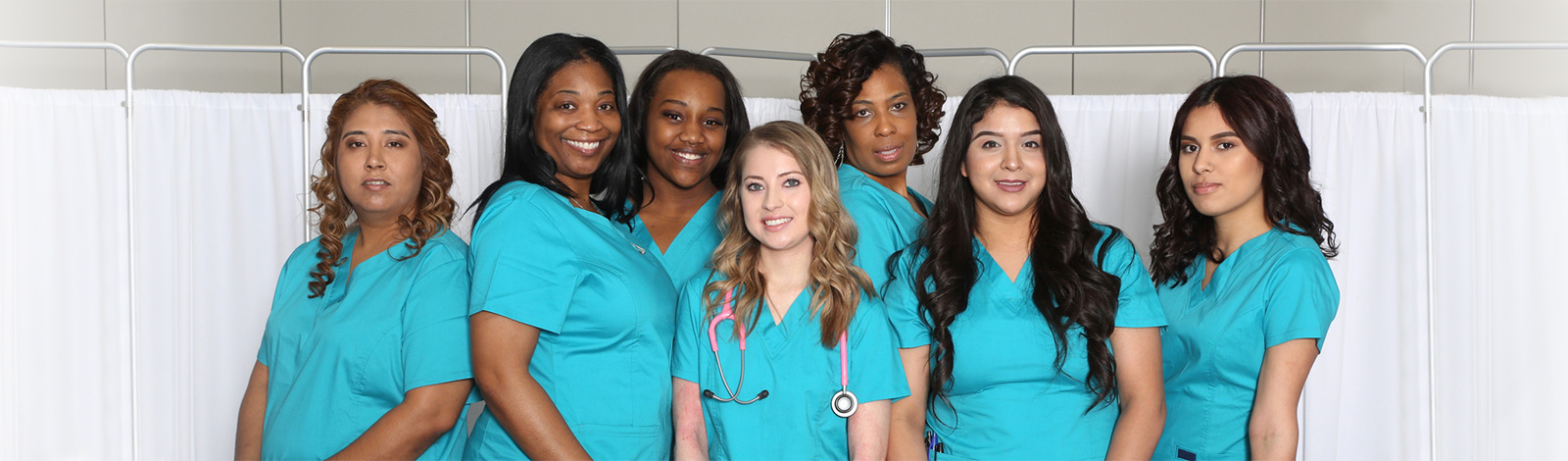 Nurses standing together smiling in a group.