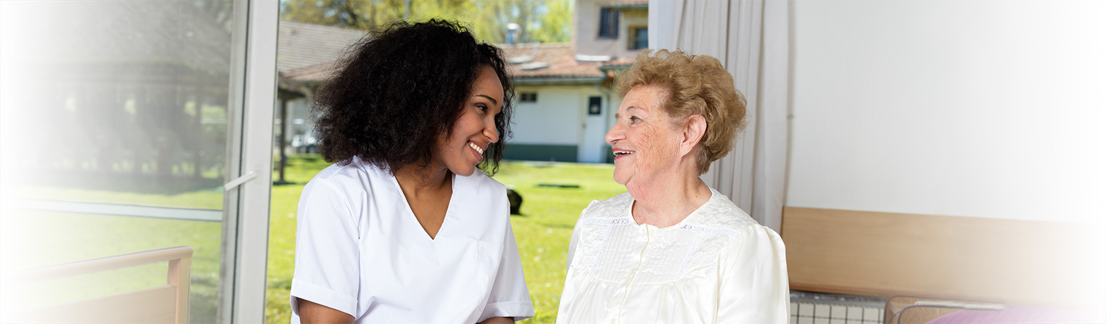 A nurse and a resident smiling together on a bed.