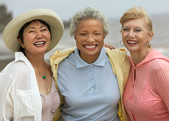 Three women standing on a beach together smiling arm in arm.