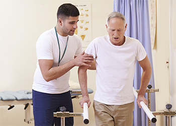 A rehab staff member assisting a patient with walking safely using the parallel bars.