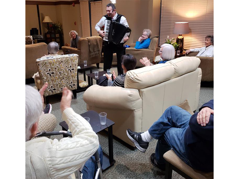 Residents listening to music from an entertainer.