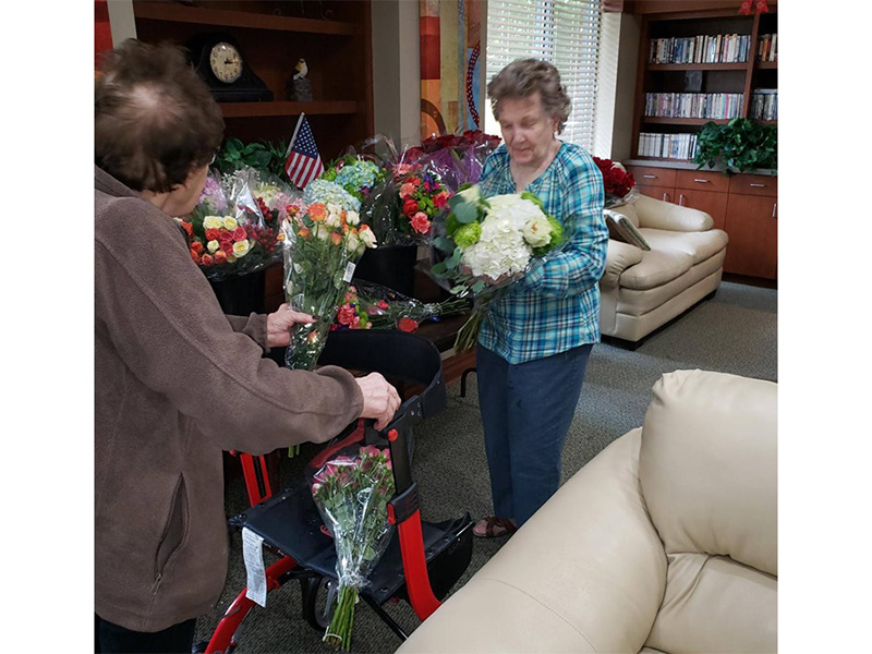 Residents sorting through bundles of flowers together.