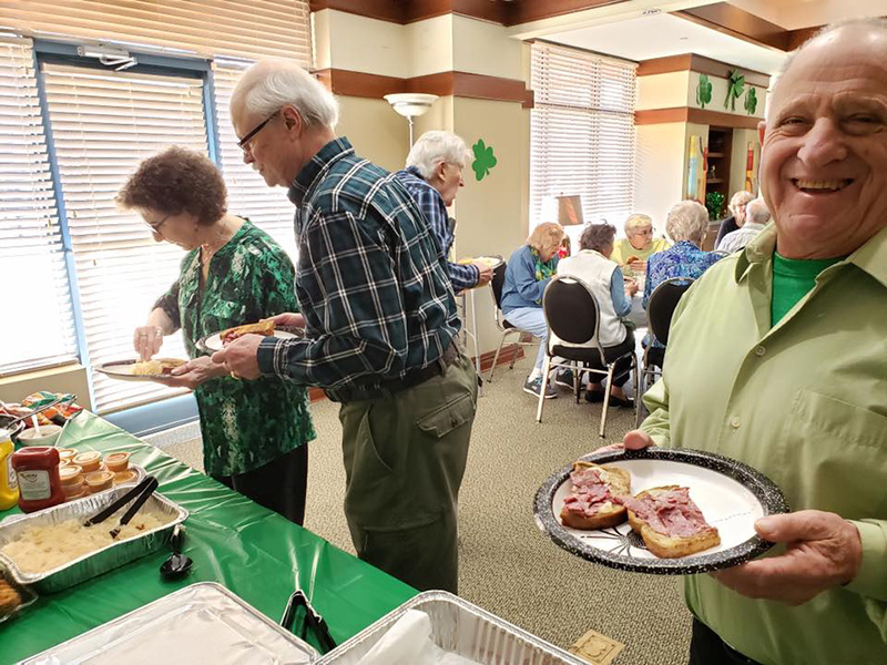Residents enjoying a St. Patrick's Day meal together.