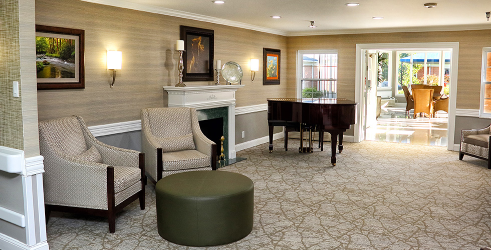 recreation room with grand piano, fireplace, and game tables