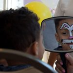 youngster admiring his face paint in the mirror