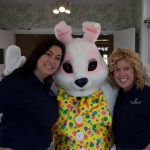 2 smiling female staff members taking a picture with the easter bunny