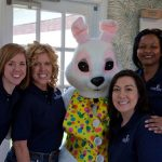 smiling staff members gathered around the easter bunny