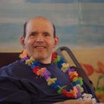 male resident wearing a lei at the party