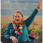resident with a lei around her neck raising her arm