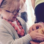 young visitor holding a baby chick