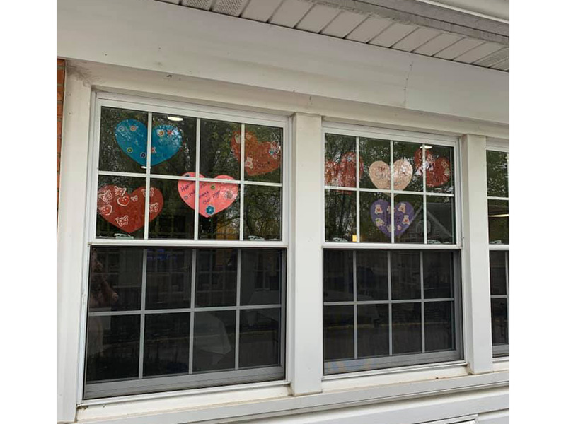 Hearts hanging in a window with words of encouragement for residents and staff.