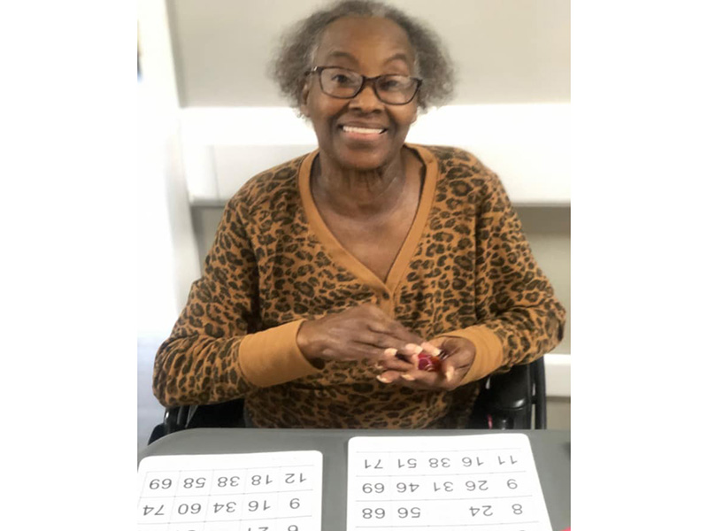 A resident smiling while playing Bingo.