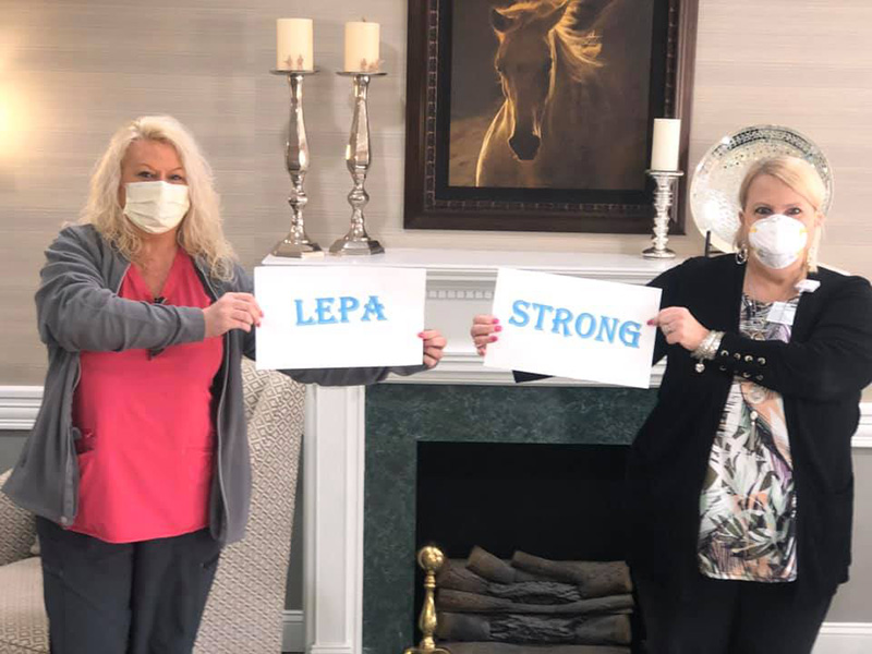 Staff holding up signs that read 'Lepa' and 'Strong'.