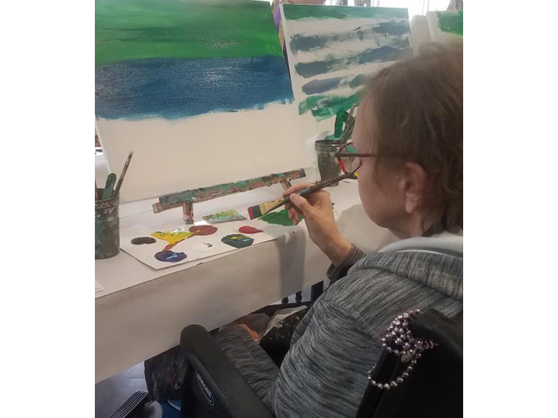 A resident painting on a canvas.