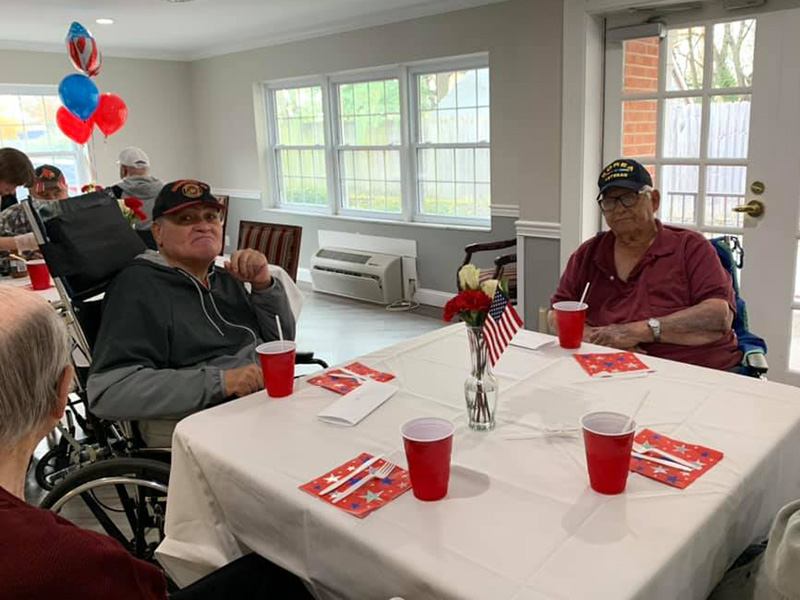 Residents sitting together at a table for a 4th of July party.