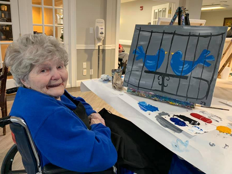Resident smiling at her completed painting of birds on a canvas.