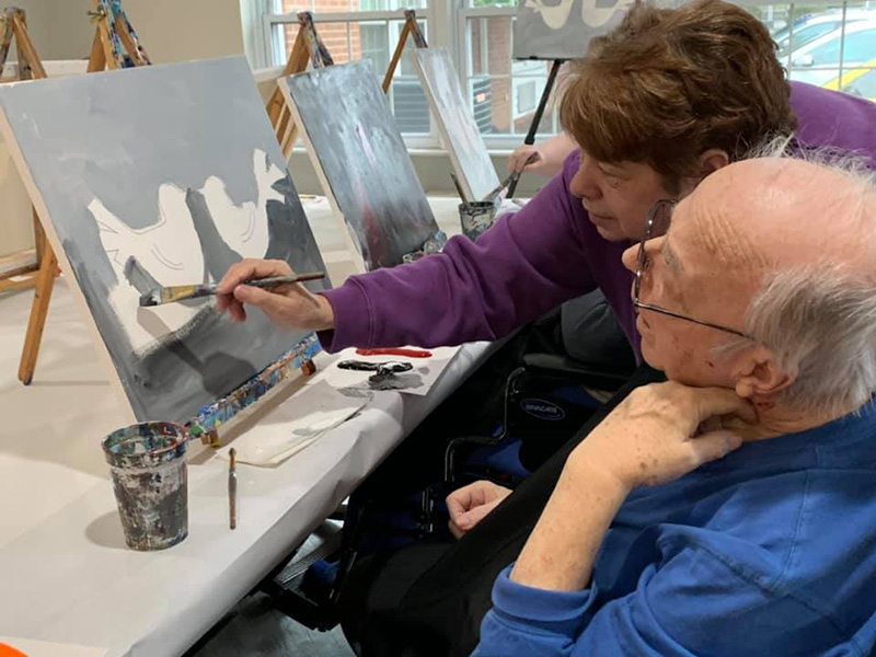 Residents painting birds on a canvas.