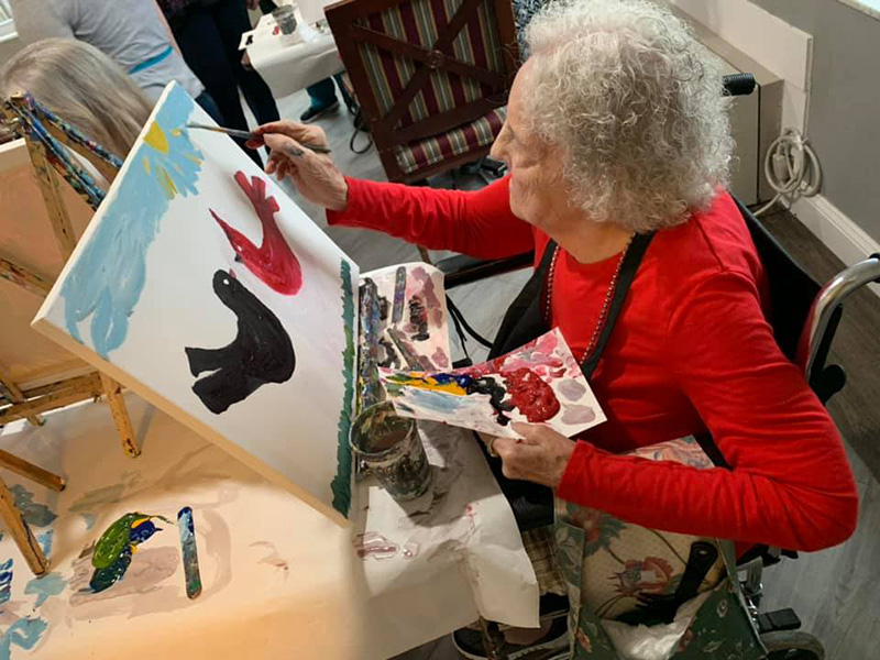 Resident painting a bird on a canvas.