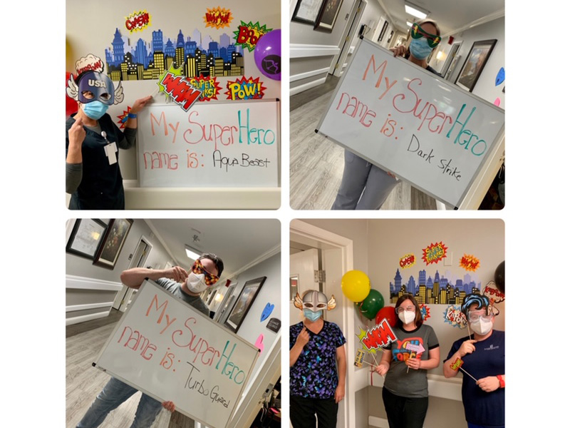 Residents and staff dressed as super heroes with superhero names on a sign beside them.
