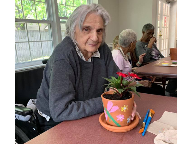 A resident who painted a pot and planted a flower in it.