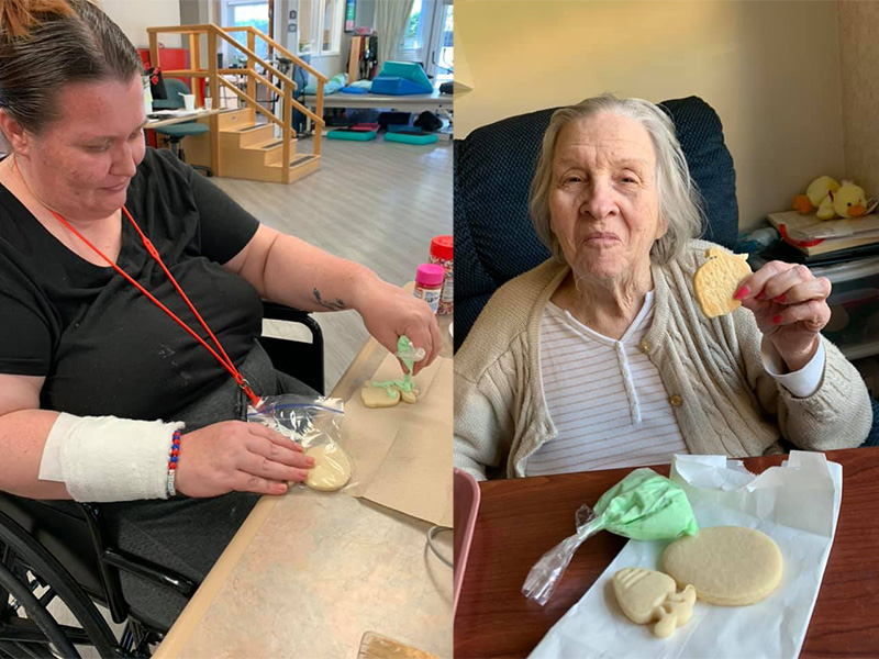 Two residents decorating cookies.