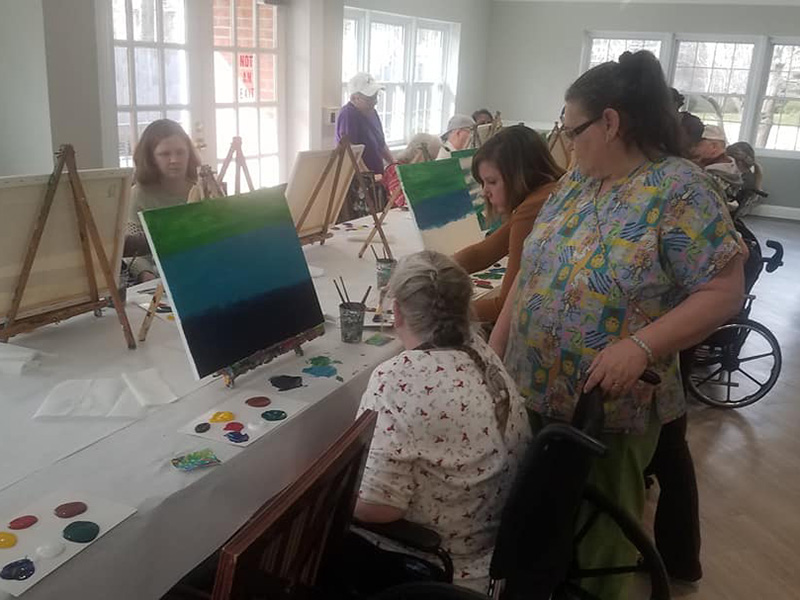 Residents painting on a canvas.