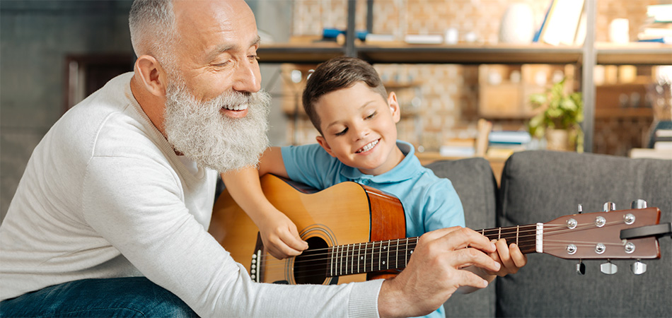 A senior helping a young boy play the guitar.