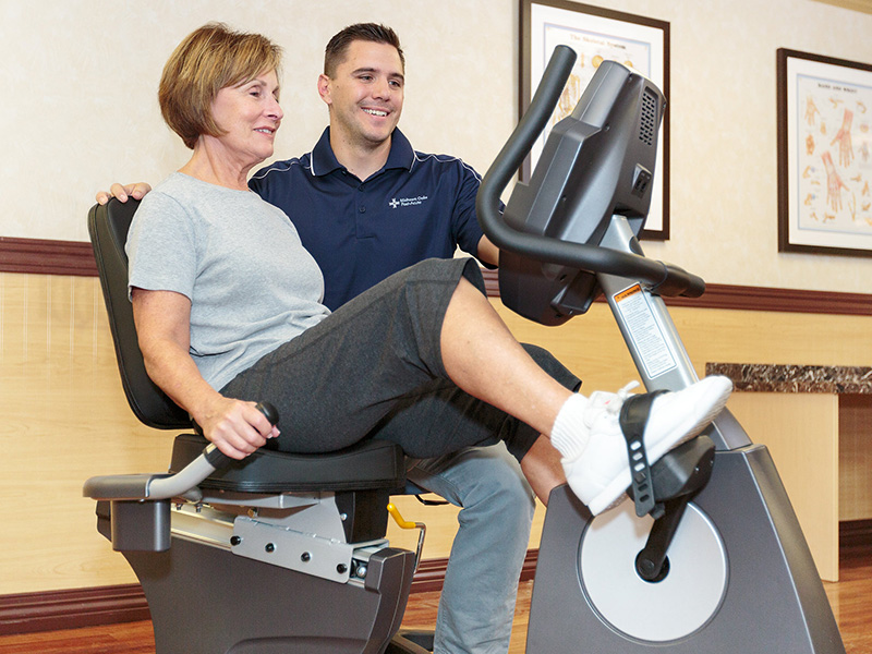 Woman pedaling a stationary bicycle in the rehabilitation room