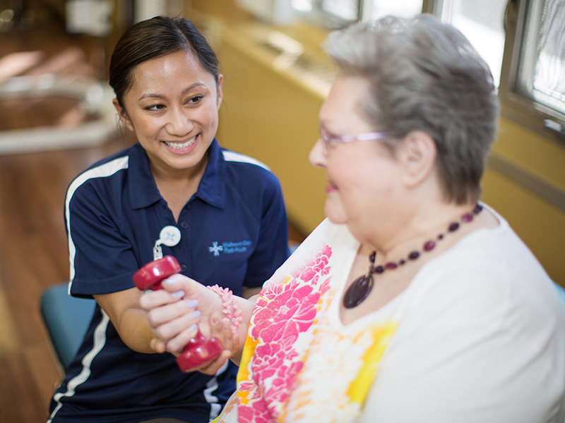 Smiling resident in a colorful Hawaiian shirt using small hand weights with a therapist