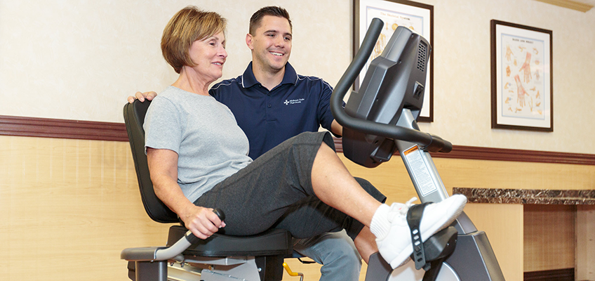 resident using an exercise bike with a therapist's supervision