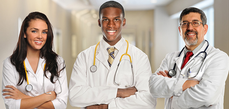 Three medical professionals wearing white lab coats and stethoscopes