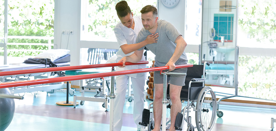 Physical therapist helping a resident out of his wheelchair while he grabs onto the parallel walking bars