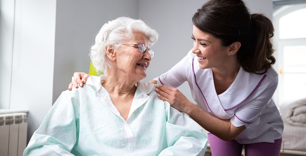 A smiling nurse leaning down to check on a happy resident