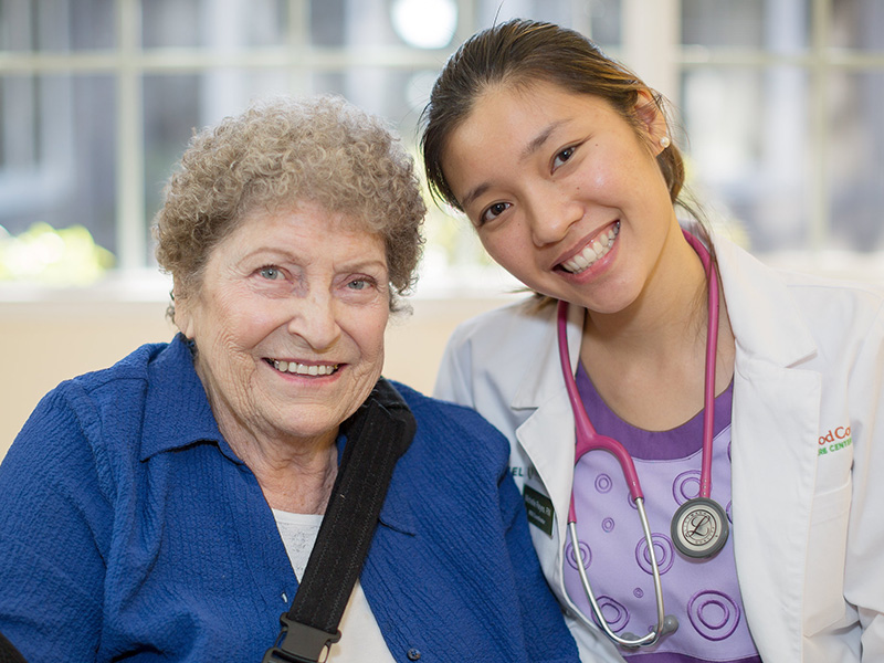 A nurse and a resident sitting together and smiling.