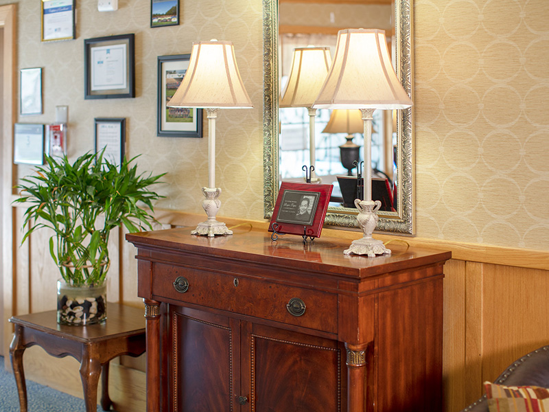 An entry way with a table, lamps that are lit and a beautiful plant in a large vase beside it.
