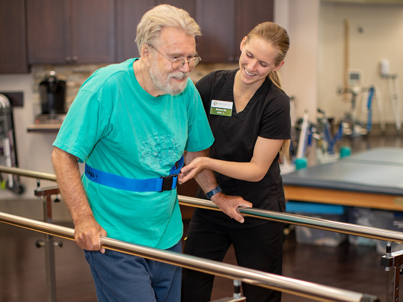Rehabilitation staff assisting a resident with parallel bar exercises.