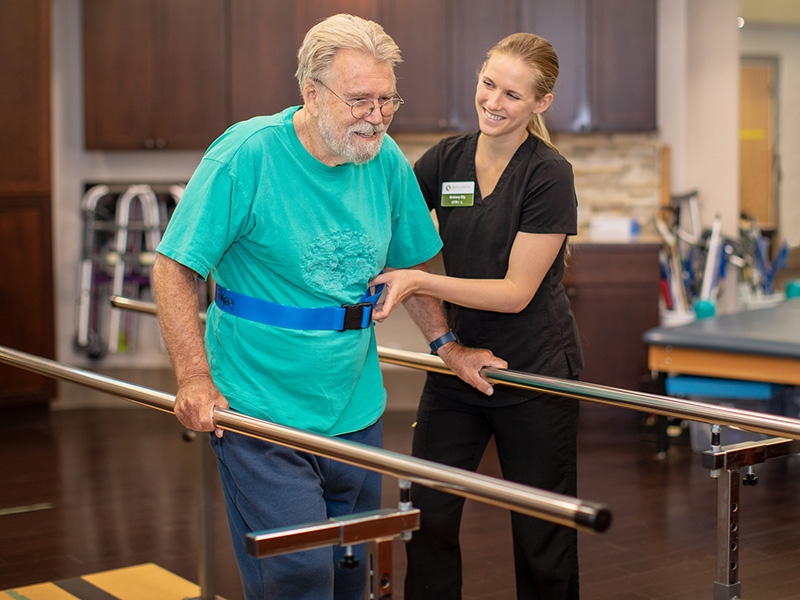 A rehabilitation staff member assisting a resident with the parallel bars