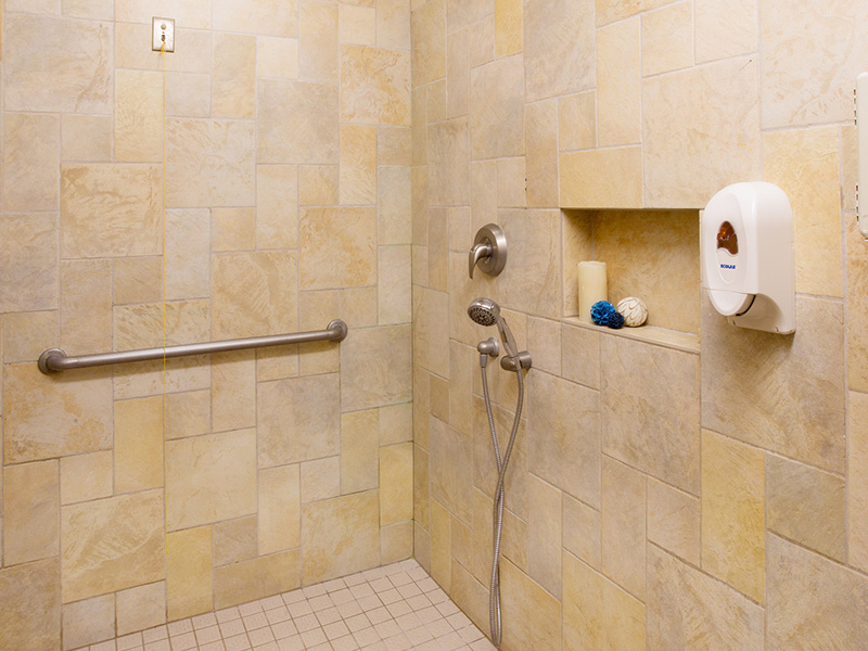 Resident shower with beautiful tiled walls and handicapped access to railing, an emergency call string and shower head.