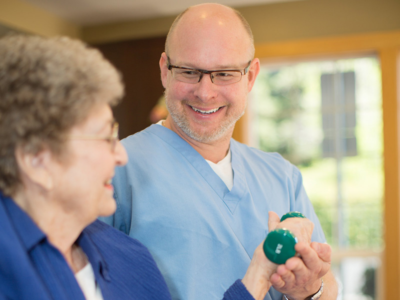 Rehabilitation staff assisting a resident with dumbbell exercises in the rehabilitation room.