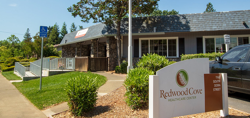 Redwood Cove Healthcare Center sign out front and handicapped access to the front of the building