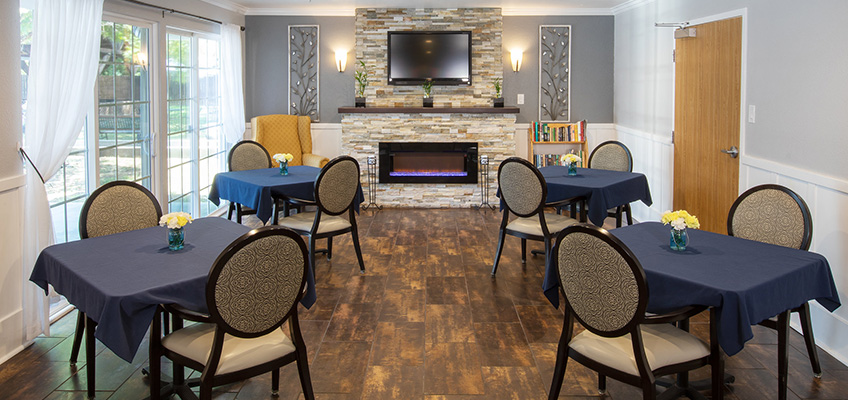 A resident dining room in front of a beautiful fireplace and beside sliding doors that lead to the outside