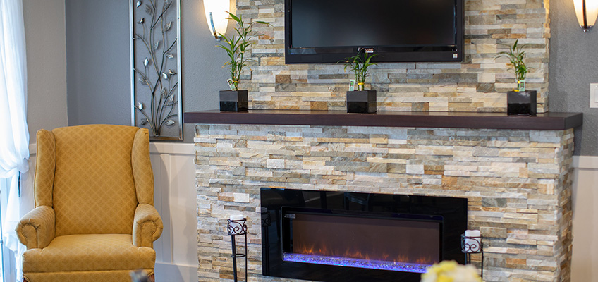 Resident lounge space with a beautiful fireplace lit and a flat screen television above it with seating beside