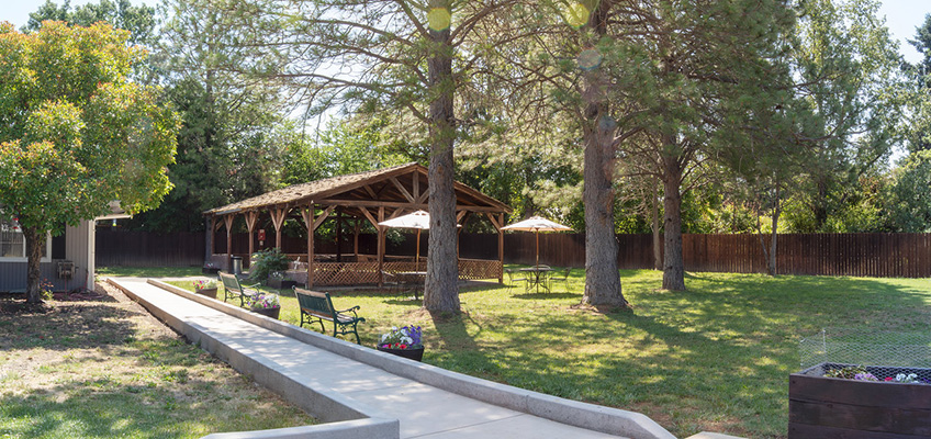 Beautiful outside space with lots of grass and a walking trail that leads to a large shaded gazebo with seating under the trees