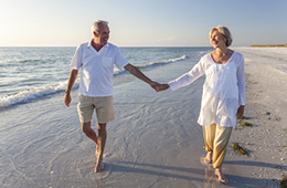 A couple walking on the beach together hand-in-hand