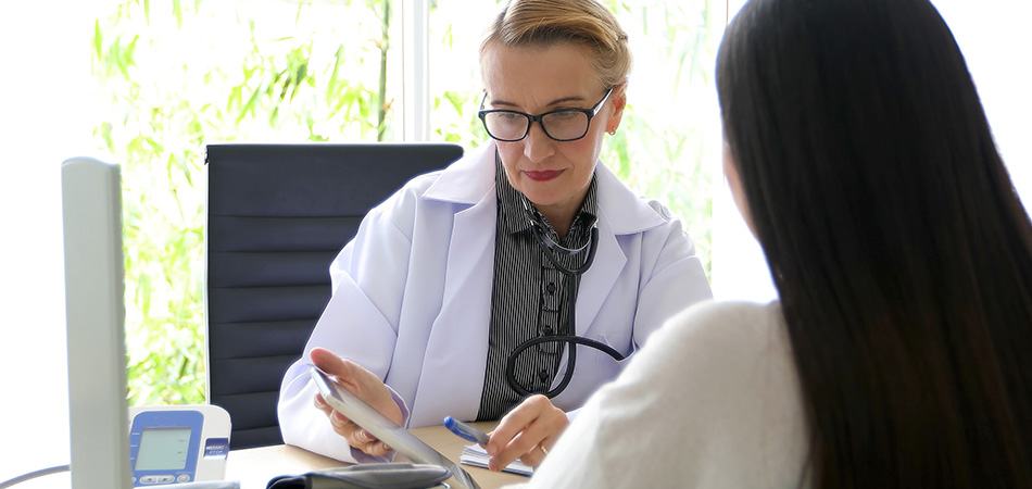 A doctor looking over a patients chart with the patient sitting at the other end of the table.