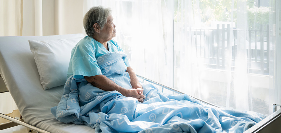 A woman sitting up in her bed staring out the window