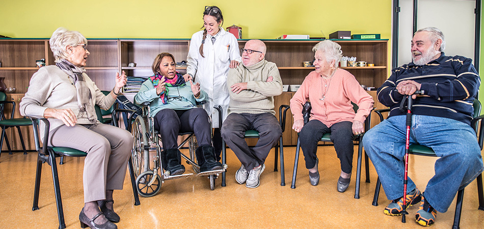 A group of seniors sitting in a half circle with a staff member talking and laughing.