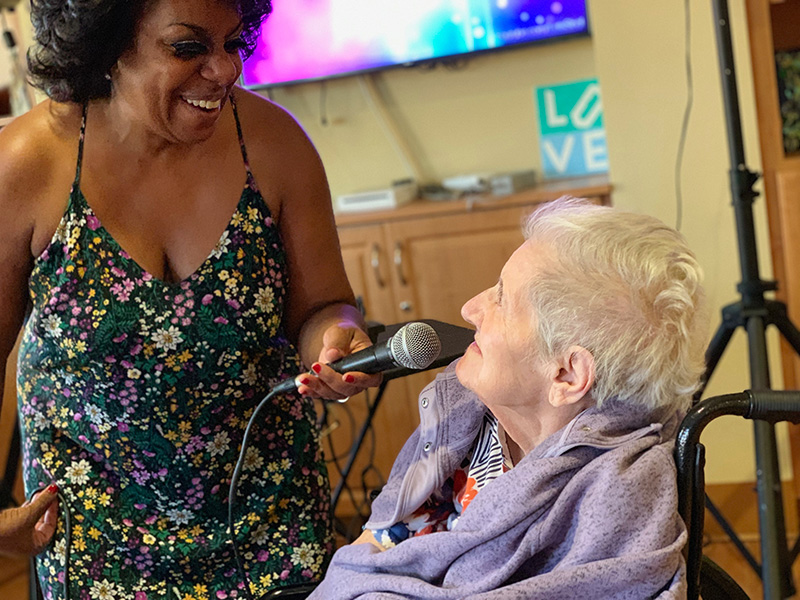 An entertainer happily holding a microphone up to a resident.